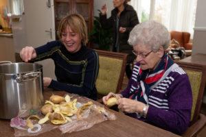Ouder schilt samen met begeleider aardappelen aan tafel